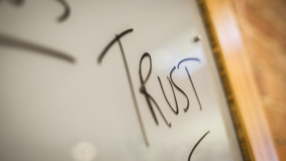 The word trust is written on a whiteboard.