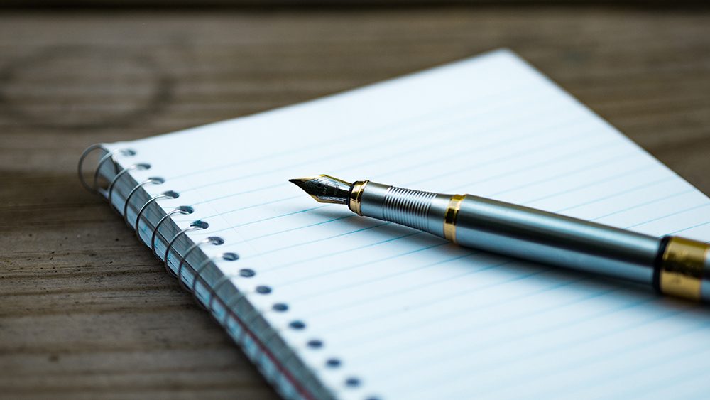 A pen sits on a blank notebook.