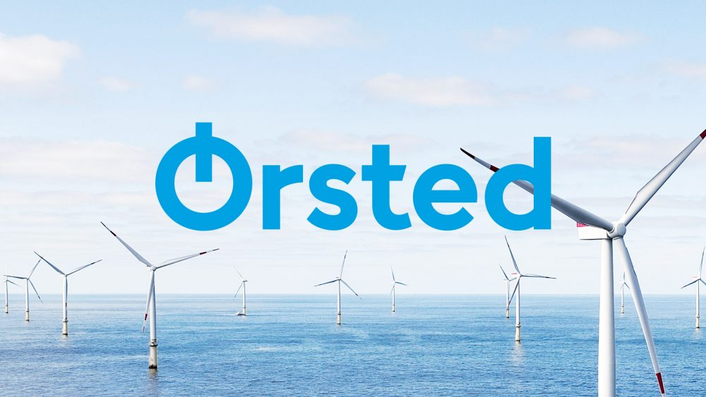 The new Ørsted logo over a field of wind turbines.