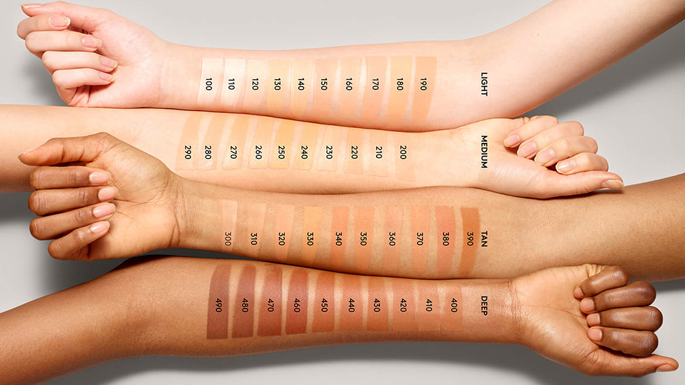 The entire Fenty Beauty line of foundations is shown on four arms, each a different skin tone.