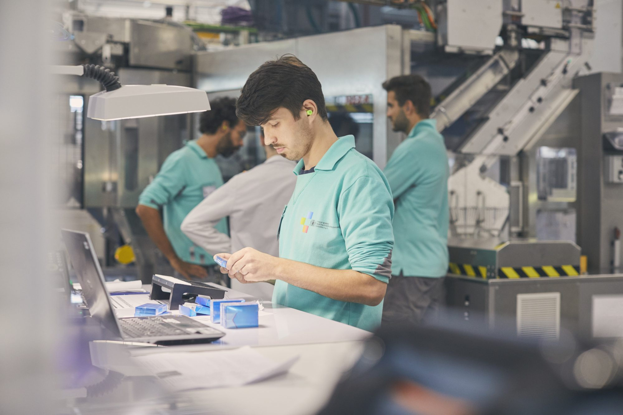 A PMI employee works in a factory.