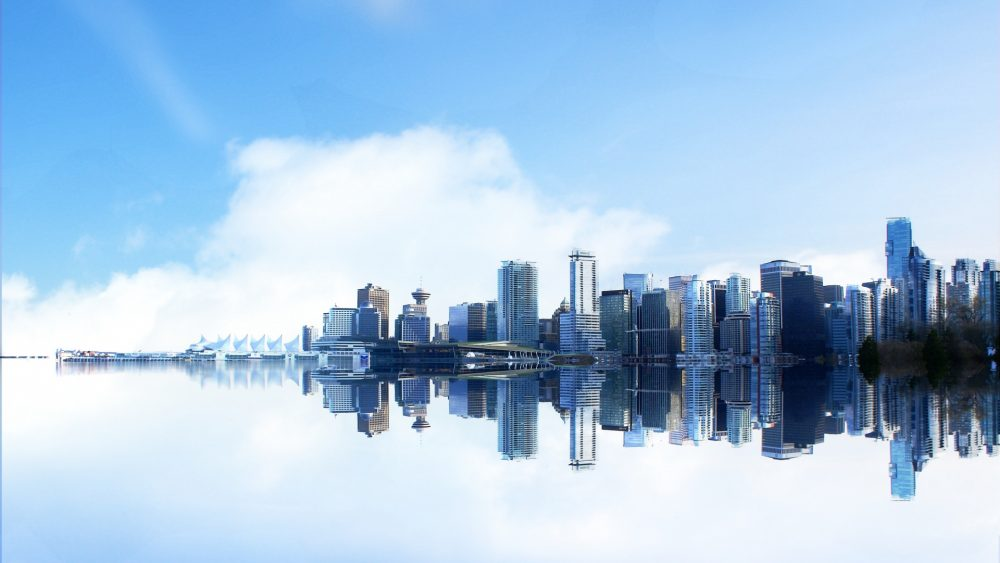 The Vancouver skyline is reflected in the harbour.