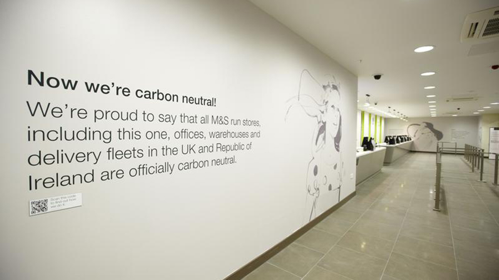 A decal on a wall in a Marks and Spencer store explains the operation is carbon neutral.
