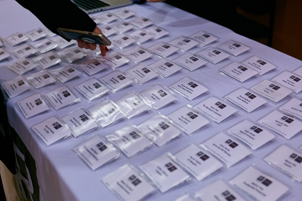 A conference attendee collects a name badge from a table.